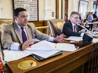 Rep. Jason Villalba, R-Dallas, left, talks with fellow representatives at his desk during the final days of the 84th Texas legislature regular session on Friday, May 29, 2015 at the Texas state capitol in Austin, Texas.  At right is Rep. Tony Dale, R-Cedar Park.