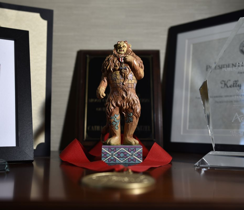 A small statue of the Cowardly Lion from the story of the Wizard of Oz sits alongside several awards in Kelly Rentzel's office as a reminder of the courage she has gained on her mental health journey.