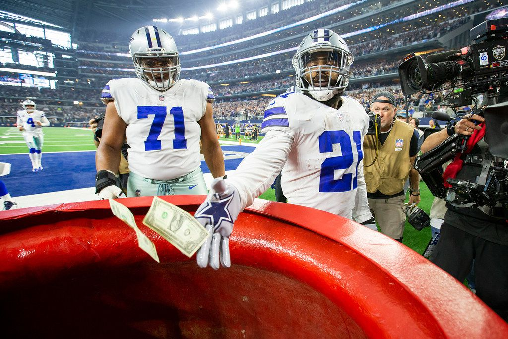 FILE - Cowboys running back Ezekiel Elliott (21) drops $21 into the Salvation Army kettle after scoring a touchdown as offensive tackle La'el Collins (71) looks on during the first quarter of a game against the Washington Redskins at AT&T Stadium on Thursday, Nov. 22, 2018, in Arlington. (Smiley N. Pool/The Dallas Morning News)