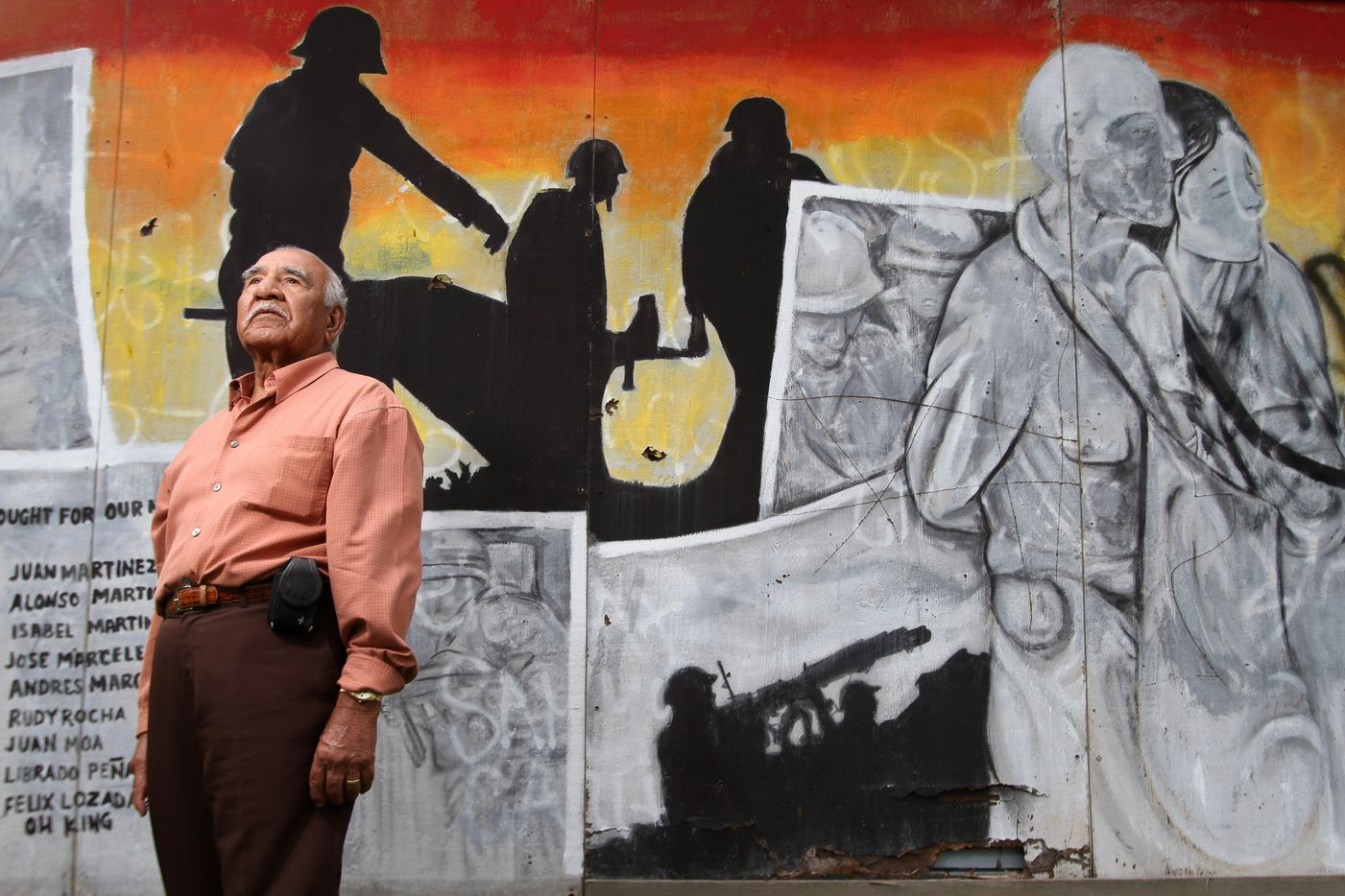 Felix Lozada, 89, a war veteran of World War II, near a mural that bears his name along with other war veterans, on Nov. 7, 2011 in West Dallas.