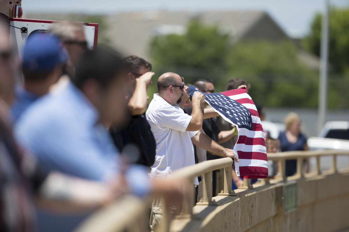 Bill Purdom, and son Tyler, from Rowlett, Texas holds a flag over US hwy 75 during the funeral procession of Dallas police Sr. Cpl. Lorne Ahrens at  on July 13, 2016 in Richardson, Texas.