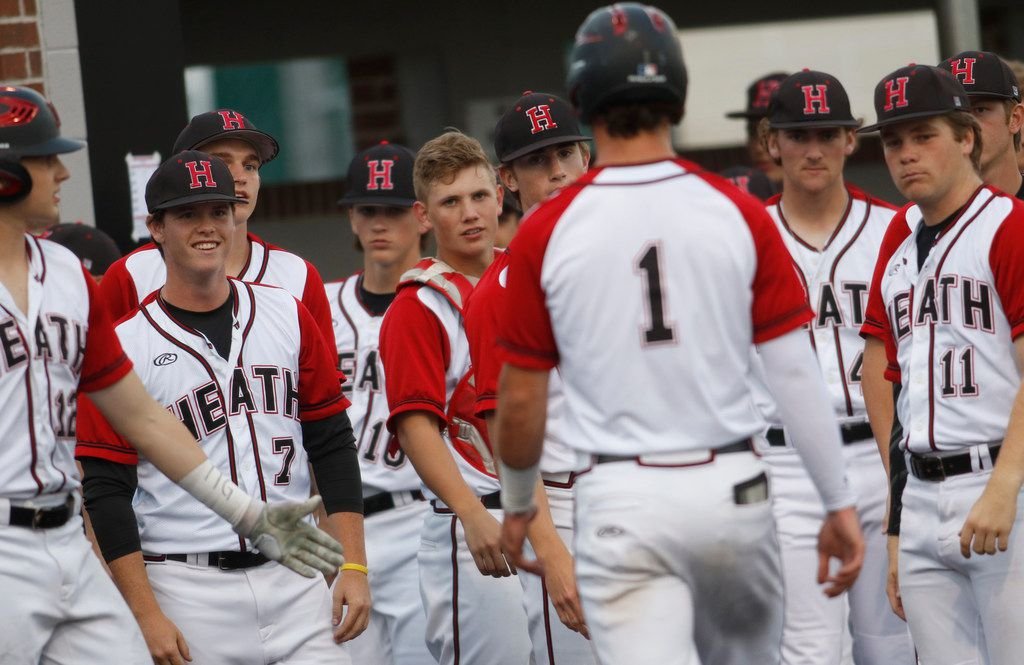 Rockwall Heath outfielder Casey Curtain (1) was greeted by stares from his teammates after he scored the team's first run on a wild pitch during the bottom of the first inning of play against The Colony.  The two teams played their non-district baseball game at Rockwall Heath High School in Rockwall on April 16, 2019. (Steve Hamm/ Special Contributor)