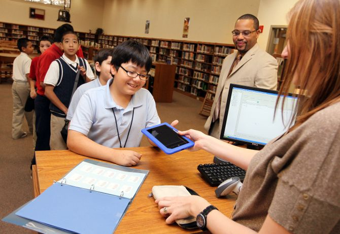 Pablo Zurita, a sixth-grader at John F. Kennedy Middle School in Grand Prairie ISD, returns a Nook e-reader to Emily Wallace, an instructional media specialist. The school district will implement some COVID-19 protocols in August when school returns such as cleaning electronic equipment as needed.