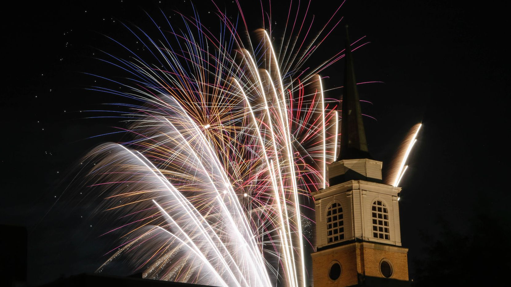 Fireworks illuminate the First Baptist Church Arlington's steeple during a Fourth of July fireworks show in 2019.