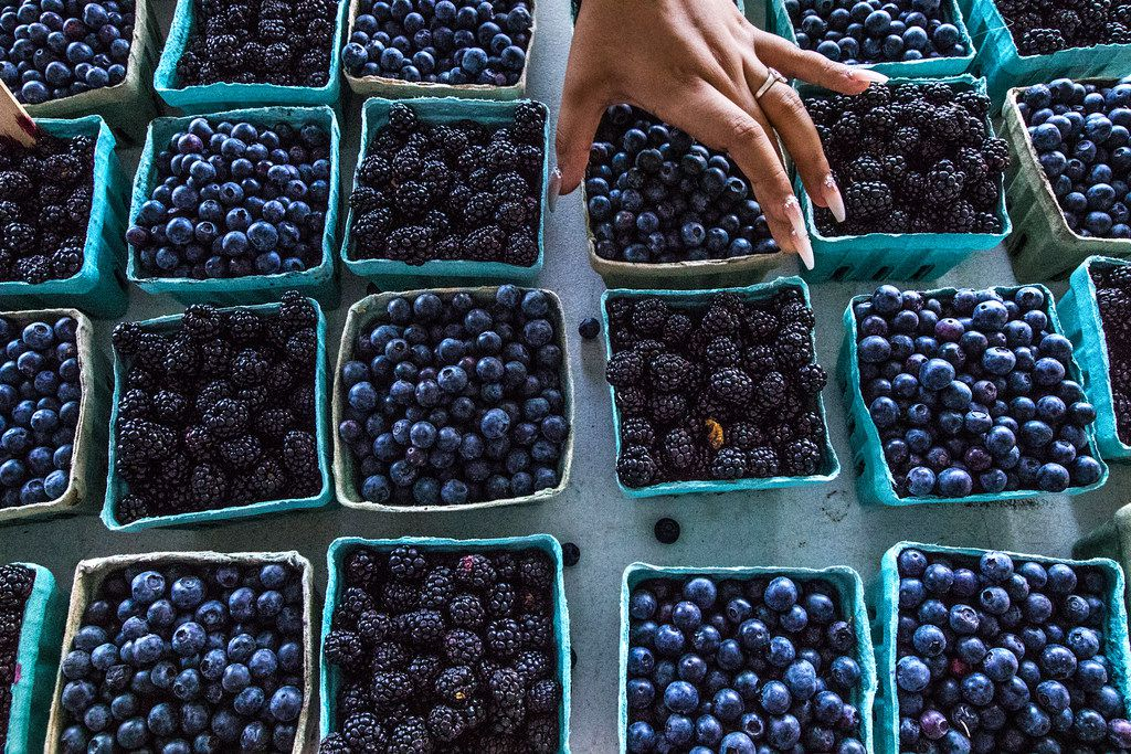 Helen Castillo, of Dallas, straightens baskets of berries at The Shed at Dallas Farmers Market in Dallas on June 9, 2018.