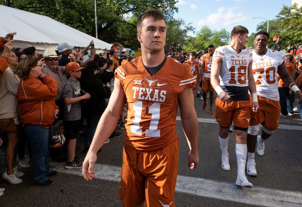 University of Texas quarterback, Sam Ehlinger, and members of the Longhorns football team march along Bevo Boulevard past fans on their way to the team locker room before the start of the Orange and White spring game held at Darrel K Royal Texas Memorial Stadium on Saturday, April, 13, 2019, in Austin, Texas.  (Rodolfo Gonzalez/ Special Contributor)