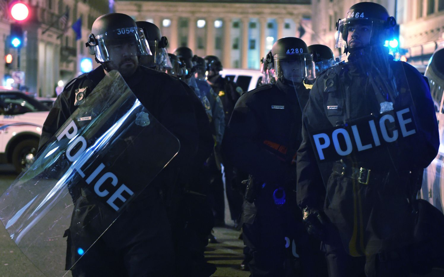 Police look on as activists rally during a Deplorable ball protest in a street outside press club in Washington, DC on January 19, 2017.