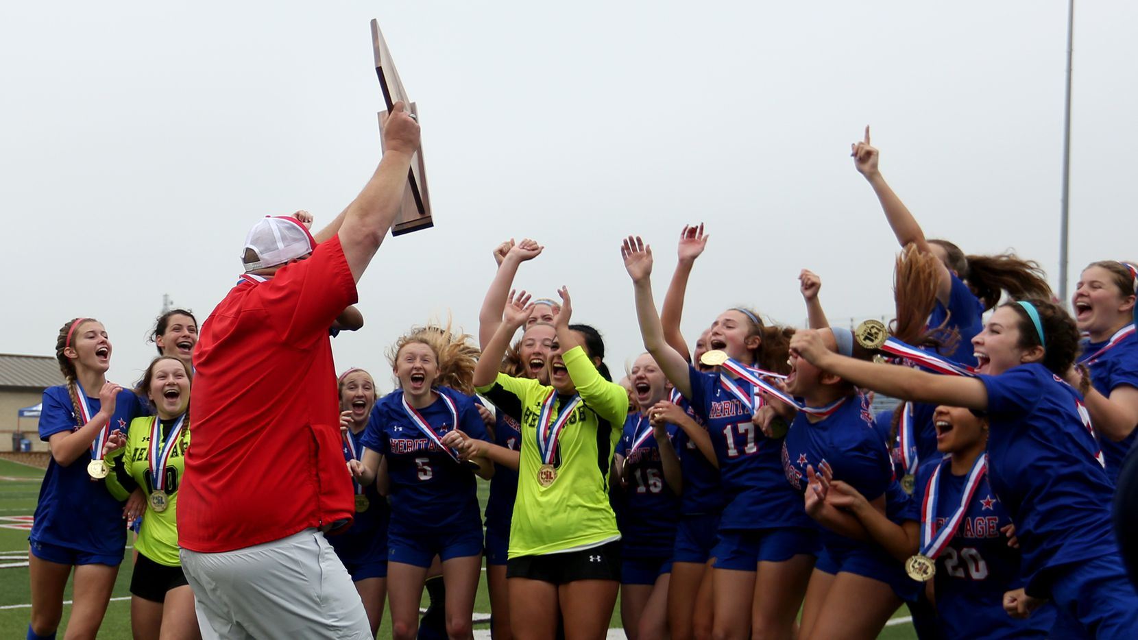 Midlothian Heritage head coach Gerald Slovacek cheers with his players as he holds up the trophy during their win over Calallen at their UIL 4A girls State championship soccer game at Birkelbach Field on April 16, 2021 in Georgetown, Texas.