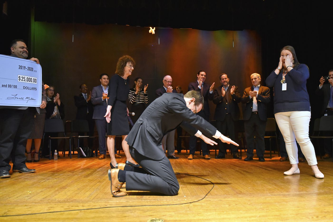 Texas education commissioner Mike Morath bows in front of Susan Moreno, right, a J.L. Long Middle School Spanish teacher, as she is honored as one of the nation's best educators. She was named the 2019 Milken Educator Award winner, a prize that comes with a $25,000 check.