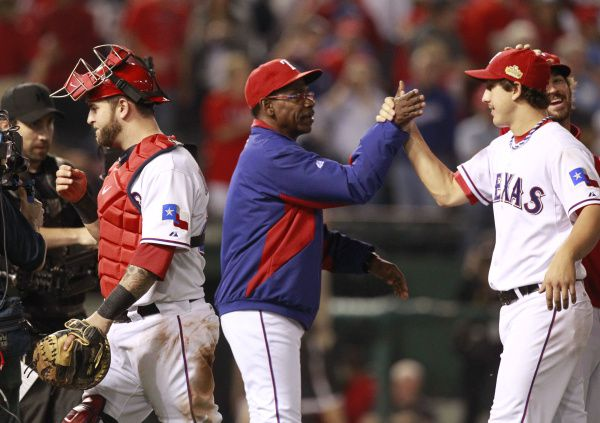 Texas Rangers manager Ron Washington congratulates pitcher Derek Holland as Mike Napoli walks by on the left, after they defeated the St. Louis Cardinals 4-0 during Game 4 of the World Series.