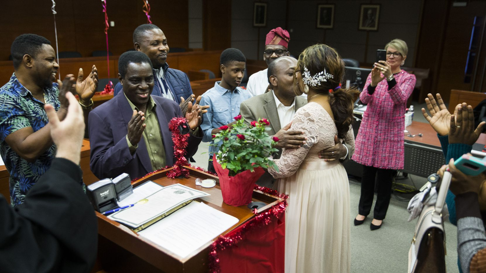 Bin Mazola and Titilope Oluyemi kissed as their families applauded after they were married by Judge Martin Hoffman on Feb. 14, 2020, at the George L. Allen Sr. Courts Building in Dallas. Hoffman performed the ceremonies for free on Valentine's Day.
