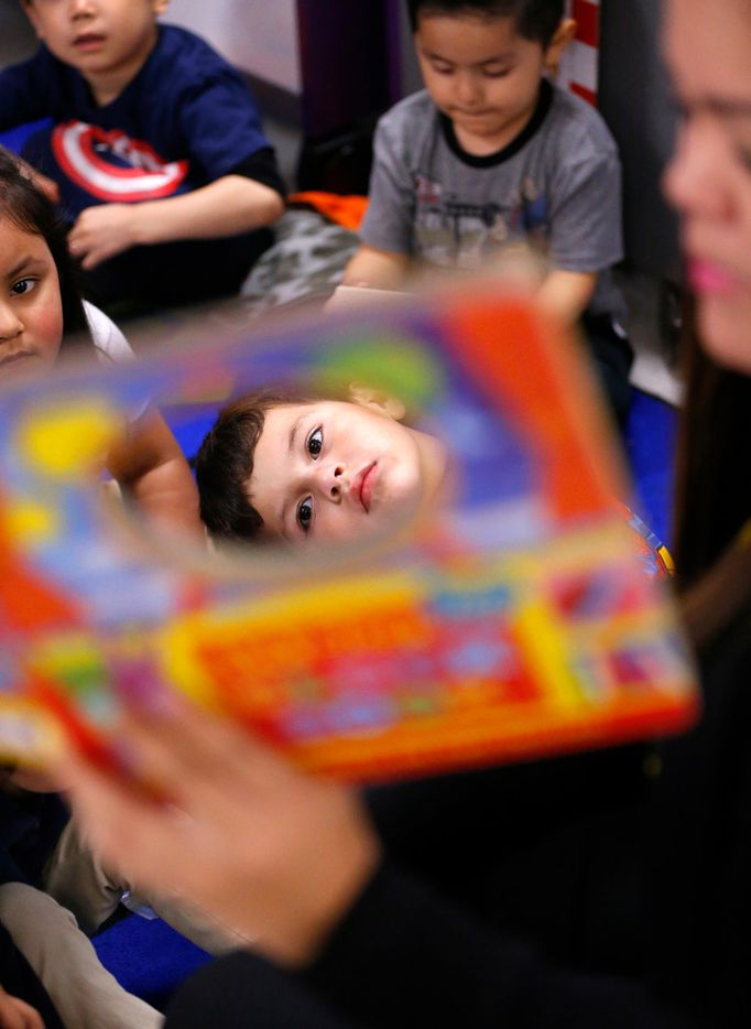 Pre-K student Ibarra Isaias (center) listens to his teacher Ana Perez Garcia read from the Tick Tock Clock Book during a lesson at Arlington Park Early Childhood Center in Dallas, Wednesday, March 27, 2019.