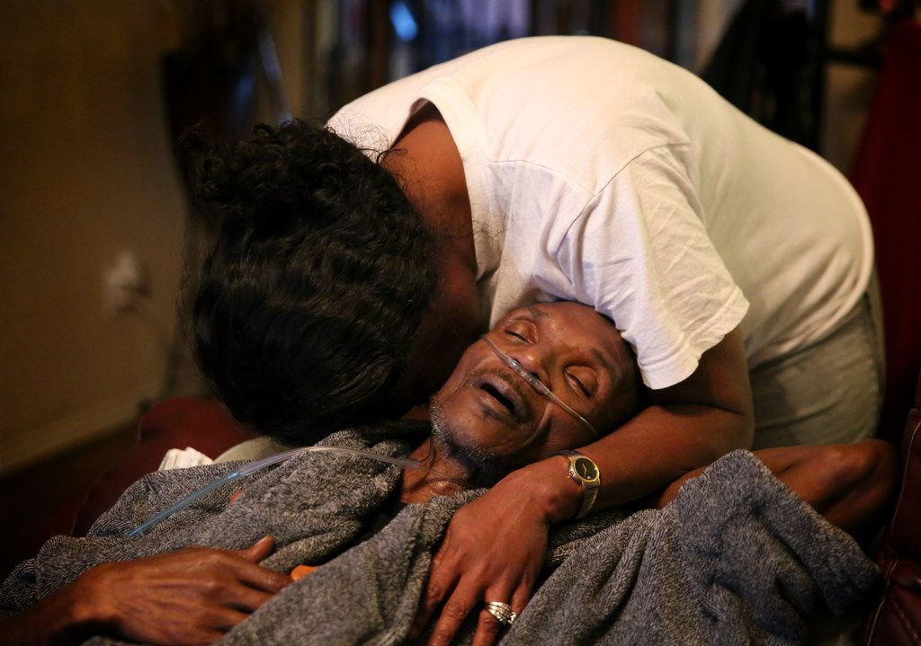 Sherita Lindsey, wife of Johnnie Lindsey, a Dallas County exoneree who spent 26 years in prison for a crime he didn't commit, quietly cries while embracing her husband as he rests at their home in Dallas on Tuesday. Lindsey is in hospice at his home and is dying of liver cancer.