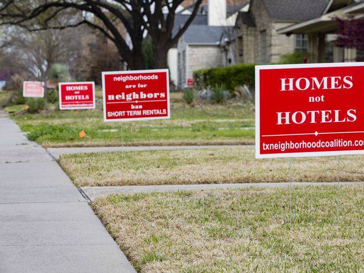 Bright-red signs protesting short-term rental properties in the neighborhood have been in place for weeks in the front yards of many homes along Prospect Avenue in Dallas' Edgemont Park Conservation District.