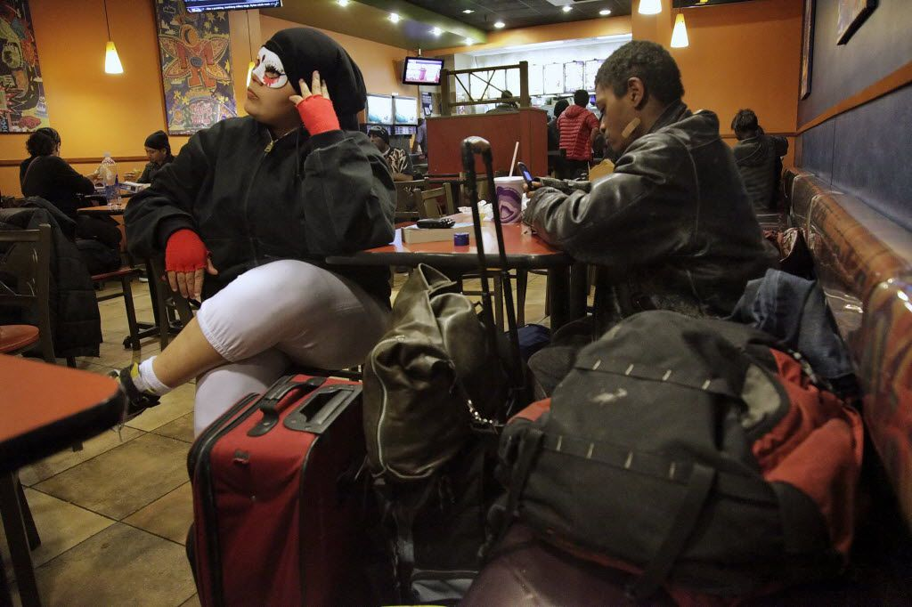 """Wearing a mask to protect her """"soul,"""" Gizmo Lopez, 19, left, who identifies herself as bisexual and homeless, sits with her boyfriend Tiny Jenkins and all their possessions inside a fast food restaurant, waiting to ride the subways for a night's sleep in New York.  Almost half of the city's homeless youth are part of the LGBT - lesbian, gay, bisexual or transgender  population. (AP Photo/Bebeto Matthews)"""