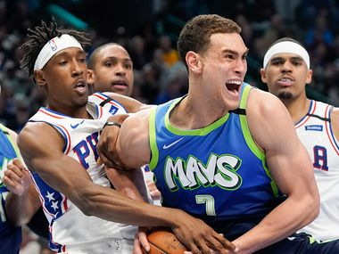 Dallas Mavericks forward Dwight Powell (7) wrestles the ball away from Philadelphia 76ers guard Josh Richardson (0) during the second half of an NBA basketball game at American Airlines Center on Saturday, Jan. 11, 2020, in Dallas.