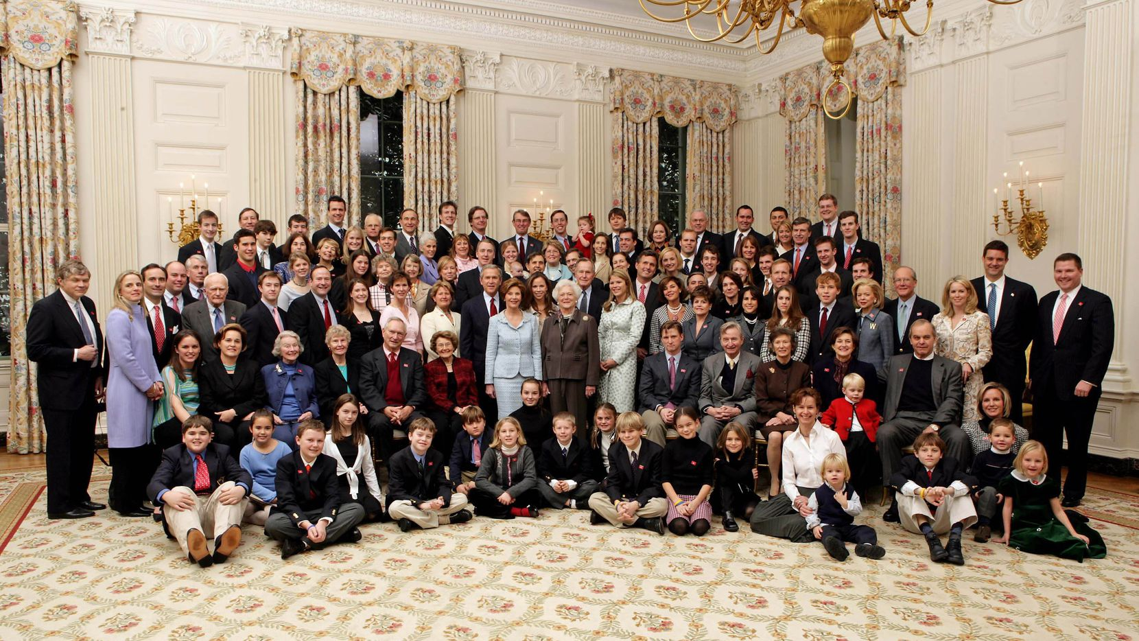 2005: President George W. Bush, Laura Bush, former President George H. W. Bush, and former first lady Barbara Bush pose for a portrait with members of their extended family in the East Room of the White House.