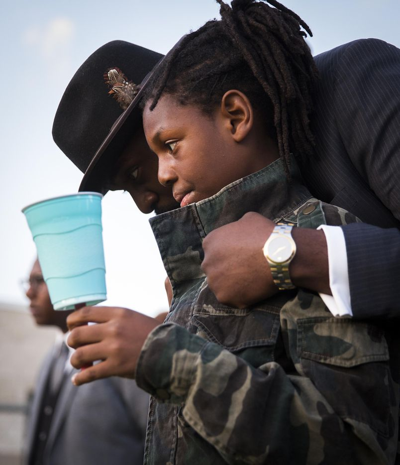 """Dr. Michael W. Waters hugs his son Jeremiah during the """"Remember His Name: Vigil for Jordan Edwards"""" candlelight vigil at Virgil T. Irwin Park on Thursday, May 4, 2017, in Balch Springs, Texas."""
