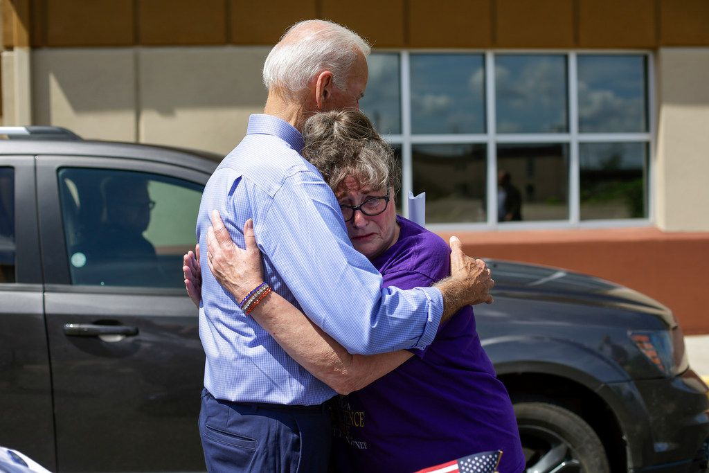 Former vice president and 2020 presidential candidate Joe Biden consoles Belinda Scavone as she speaks about the recent passing of her husband after a campaign event on July 4 in Marshalltown, Iowa. The 2020 Iowa Democratic caucuses will take place on Feb. 3, 2020.