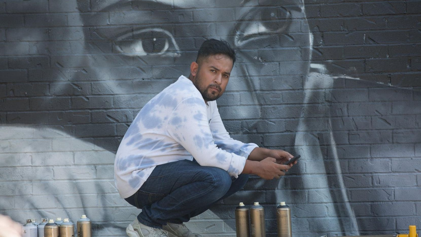 Artist Juan Velazquez poses in front of a mural he's painted in this courtesy photo.