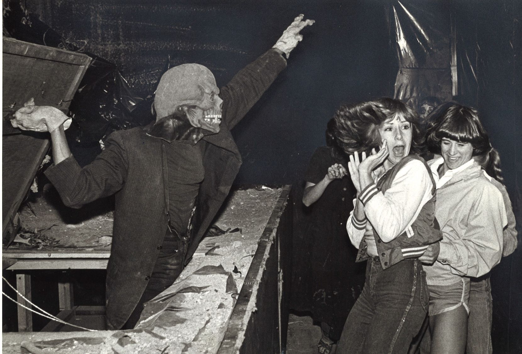 Ghoul Jerry Fleming scares Marie Rossman (center) of Carrollton and Amy Walker at the March of Dimes Haunted House on Halloween Night in 1979.