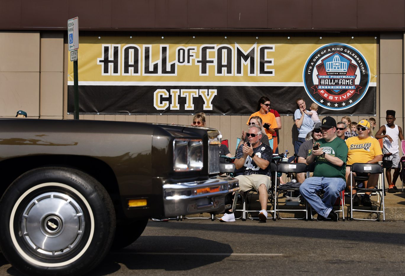NFL football fans watch as Pro Football Hall of Fame members pass by in classic cars during the Canton Repository Grand Parade in downtown Canton, Ohio, Saturday, August 7, 2021. The parade honored newly elected and former members of the Hall, including newcomers and former Dallas Cowboys players Cliff Harris, Drew Pearson and head coach Jimmy Johnson. (Tom Fox/The Dallas Morning News)