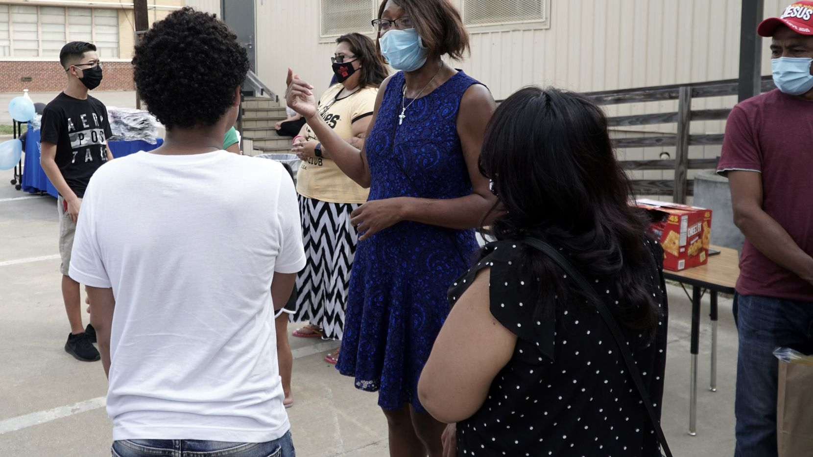 International Newcomer Academy's Principle Angelia Ross speaks with a parent and student during the Back to School Drive on the campus in Fort Worth, Texas, the weekend before classes started.