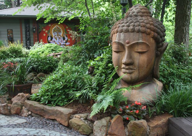 A large head of Buddha anchors the backyard garden of Brad Boling and Curtis Fesser. The mural of the Hindu diety Ganesha in the background was painted by Fesser.