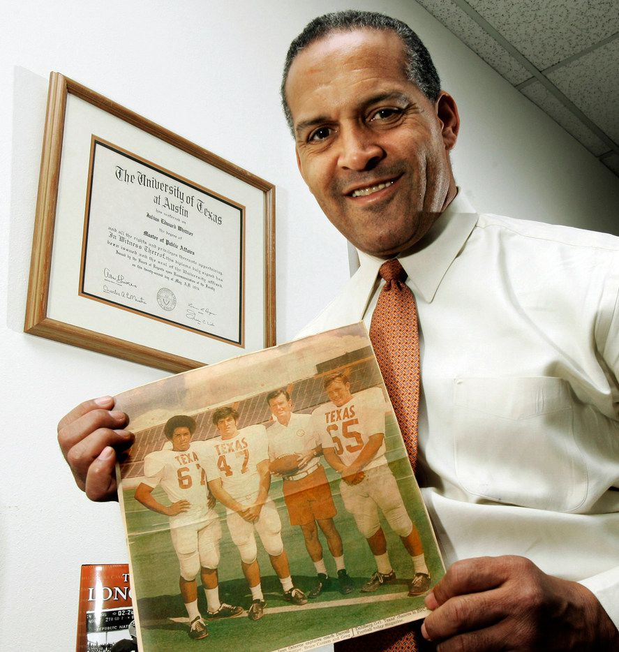 In this Dec. 16, 2005 photo, Dallas attorney and former Texas football player Julius Whittier displays a 1971 newspaper photo of himself with teammates Bruce Cannon, Greg Dahlberg, and coach Darrell Royal in Dallas. The first African-American football letterman at the University of Texas, Whittier's family later sued the NCAA on behalf of college players who suffered brain injuries.