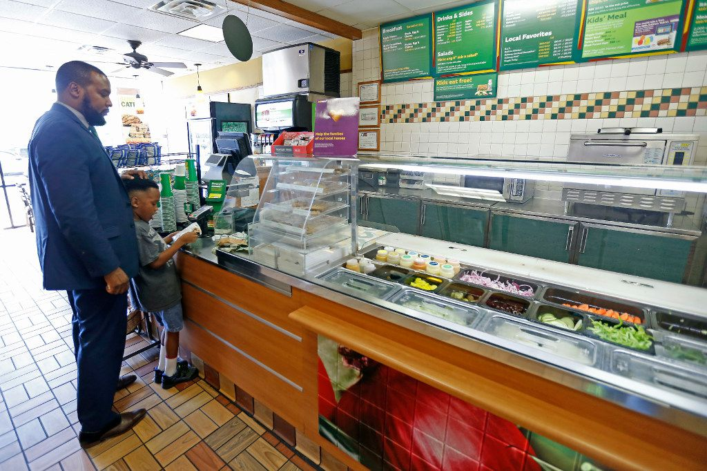 Attorney Lee Merritt (left) and his 7-year-old son Stacy Merritt, Jr., wait to pay for snacks and sandwiches at a Subway store in Allen.