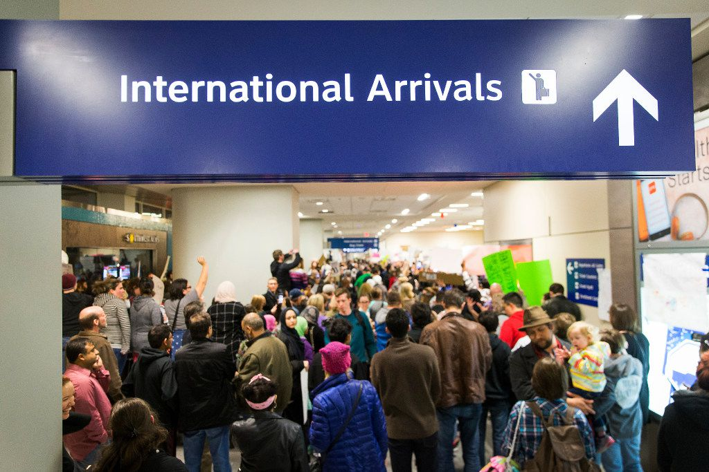 Protestors filled the international arrivals hall at DFW International Airport holds signs in opposition to President Donald Trump's executive order barring certain immigrants on Saturday, Jan. 28, 2017. (Smiley N. Pool/The Dallas Morning News)