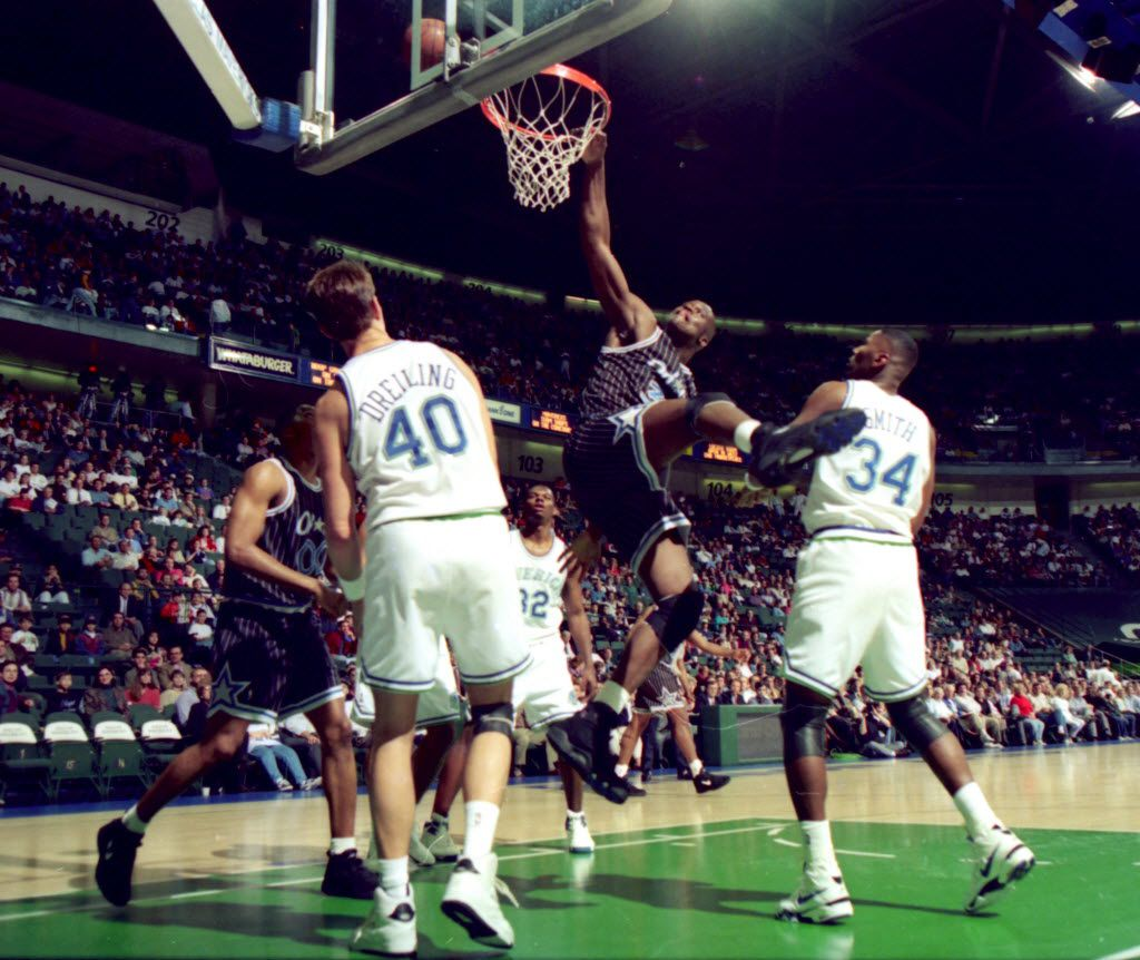 Shaquille O'Neal of the Orlando  Magic, attempts a slam dunk in the first period aganist the Dallas Mavericks at Reunion arena Thursday, March 3, 1994 in Dallas. #40, Greg Dreiling, of Dallas and #34, Doug Smith, look on.