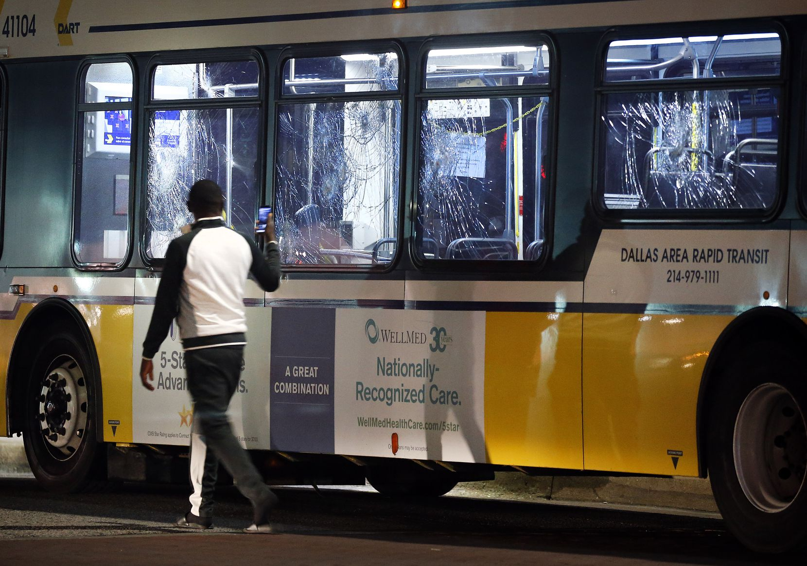 A protestor photographs a DART bus that was overrun by protestors and had the windows broken by rocks at  Wood St. and S. Lamar in downtown Dallas, Friday, May 29 2020. People were marching in protest of the in-custody death of George Floyd when they confronted Dallas Police tactical officers and tear gas was fired.