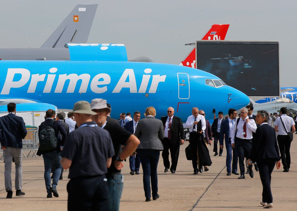 """Visitors walk past an Boeing 737-800 BCF Amazon """"Prime Air"""" cargo plane at the Paris Air Show in Le Bourget, east of Paris, France, on June 18, 2019. The world's aviation elite are gathering at the Paris Air Show with safety concerns on many minds after two crashes of the popular Boeing 737 Max."""