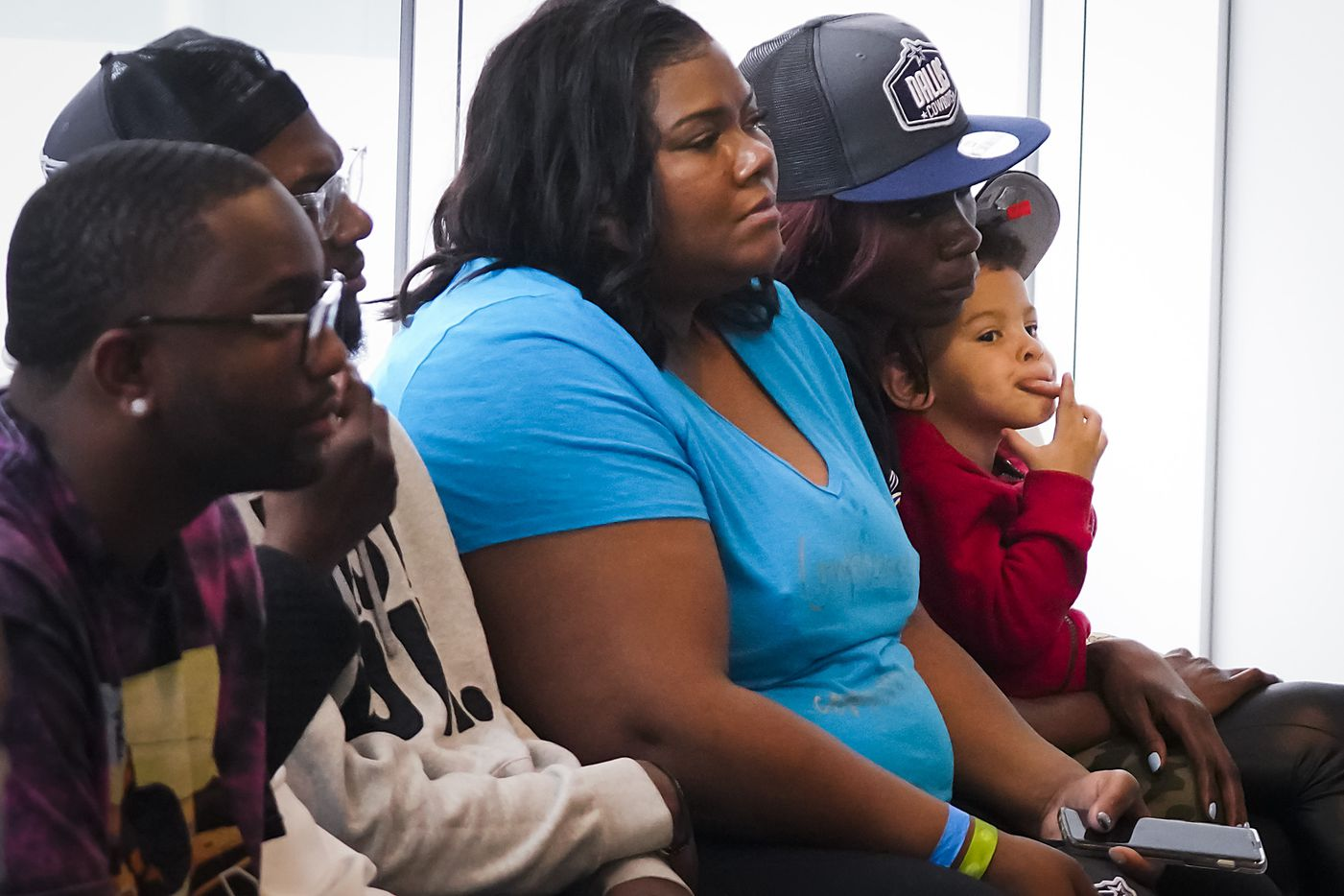 Malcolm Parsons, 3, the son of Dallas Cowboys first-round draft pick Micah Parsons, plays while sitting in the lap of his aunt Shatara Parsons who listens along with her mom Sherese Parsons, during a press conference introducing the linebacker from Penn State at The Star on Friday, April 30, 2021, in Frisco. (Smiley N. Pool/The Dallas Morning News)