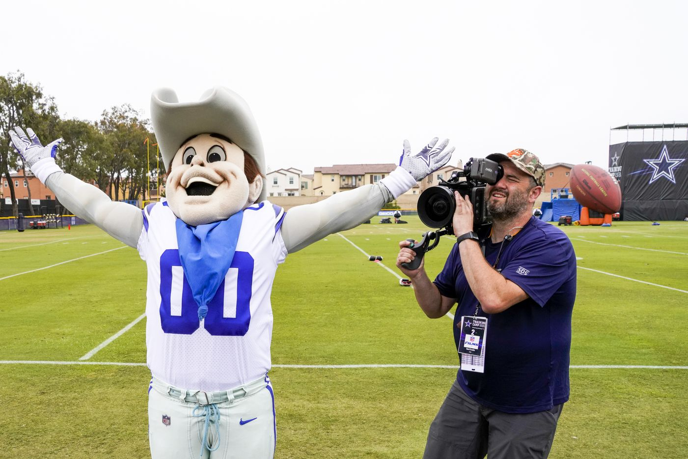 A camera operator for HBO's Hard Knocks captures Dallas Cowboys mascot Rowdy gesturing to the fans during opening ceremonies before a practice at training camp on Saturday, July 24, 2021, in Oxnard, Calif.