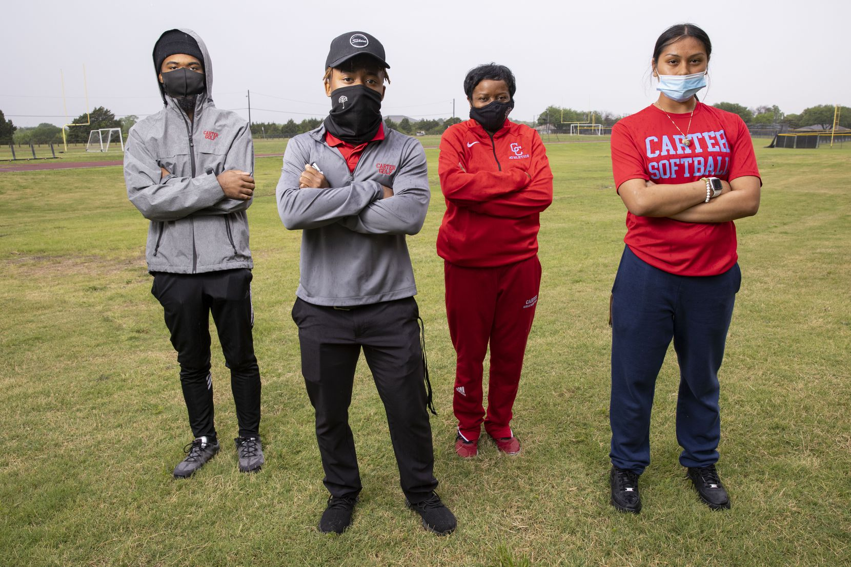 (From left) Carter High School regional golf qualifiers Glen Veasley, Jelani Rogers and Sherlyn Flores pose with coach Coach Cynthia Calahan (second to right) outside of David W. Carter High School's gymnasium in Dallas on Thursday, April 15, 2021.