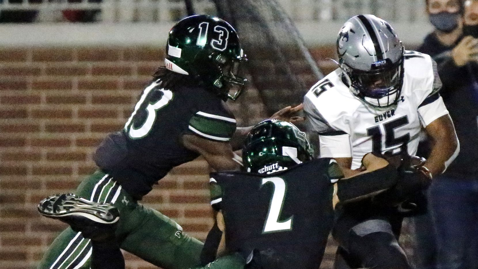 Denton Guyer High School wide receiver D'marcus Howard (15) is brought down by Prosper High School defensive back Ryan Medeiros (2) and Prosper High School defensive back Darrnell Bradshaw (13) after making the catch to set up the winning score during the second half as Prosper High School hosted Denton Guyer High School in a District 5-6A football game at Children's Health Stadium in Prosper on Friday night, October 30, 2020.