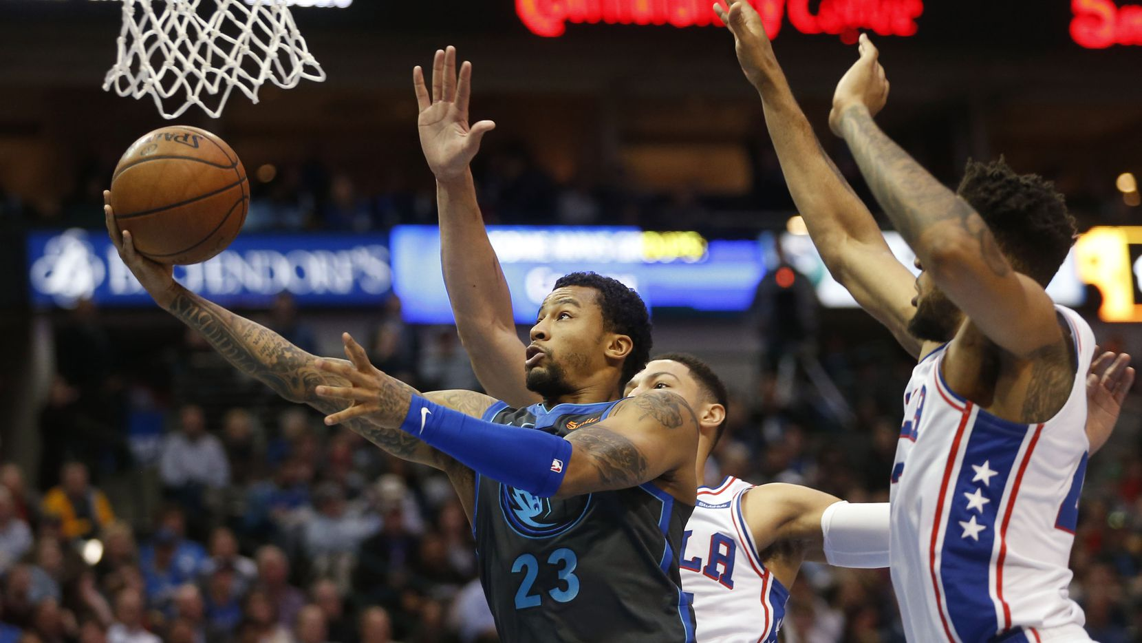 Dallas Mavericks guard Trey Burke (23) attempts a layup in front of Philadelphia 76ers guard Ben Simmons (25) and Philadelphia 76ers forward Jonah Bolden (43) during the first half of play at the American Airlines Center in Dallas on Monday, April 1, 2019. (Vernon Bryant/The Dallas Morning News)