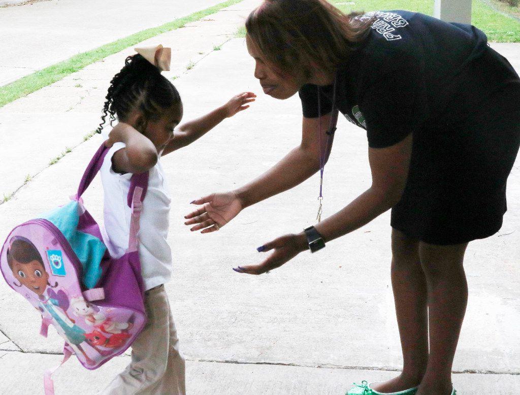Principal Onjaleke Brown greets student Skylar Thompson as she arrives at Harllee Early Childhood Center in Oak Cliff.