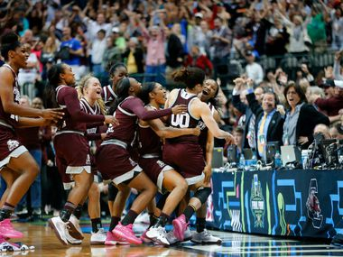 Mississippi State Lady Bulldogs guard Morgan William (2, right) is mobbed by teammates after scoring the winning basket in overtime against the Connecticut Huskies in their NCAA Women's Final Four semifinal game at the American Airlines Center in Dallas, Friday, March 31, 2017. Mississippi State broke Connecticut's winning streak with a 66-64 win. (Tom Fox/The Dallas Morning News)