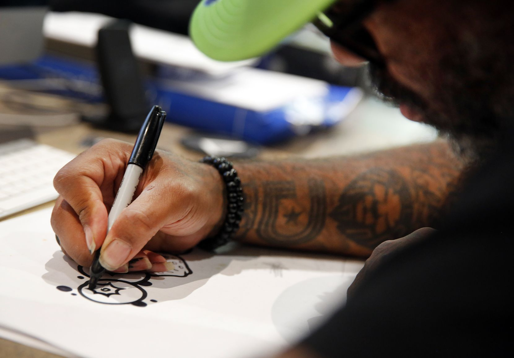 Tex Moton uses a Sharpie to create a new design.
