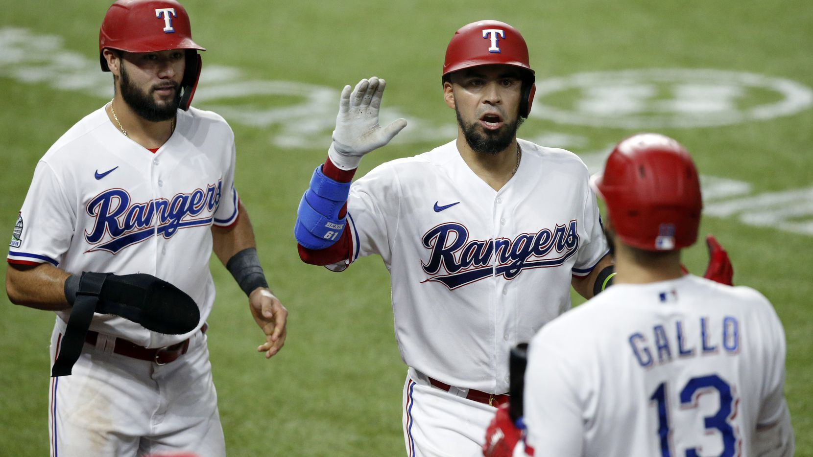 Texas Rangers short stop Isiah Kiner-Falefa (left) and Robinson Chirinos (center) are congratulated by teammate Joey Gallo (13) after scoring during the fifth inning at Globe Life Field in Arlington, Texas,Tuesday, August 25, 2020.