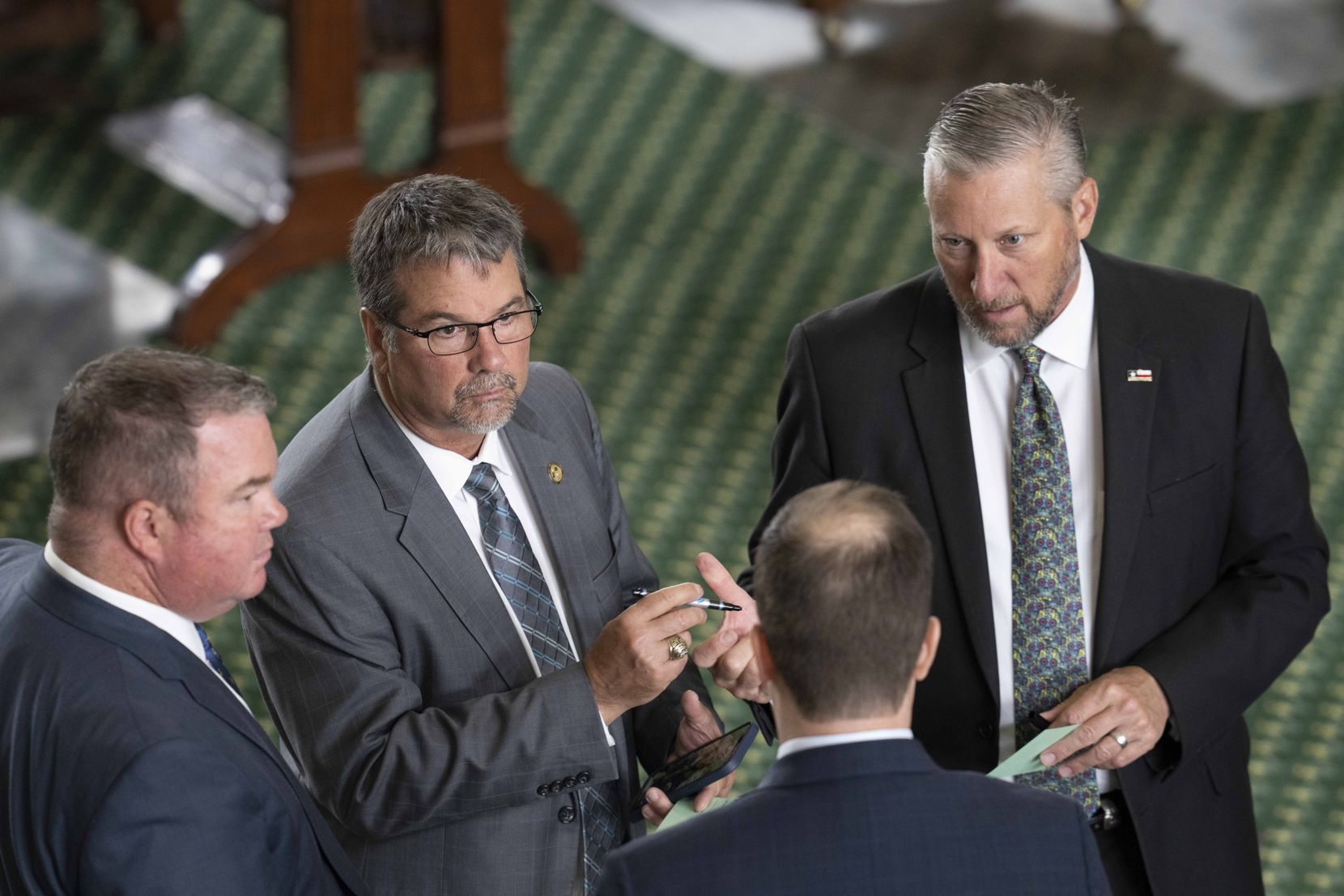 Sens. Charles Perry, R-Lubbock, (holding pen) and Drew Springer, R-Muenster, (right) talked with aides on the Senate floor Thursday.