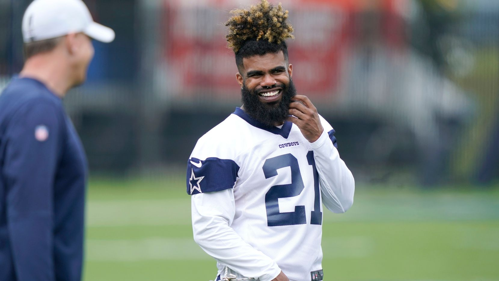 Dallas Cowboys running back Ezekiel Elliott smiles as he warms up during an NFL football team practice Wednesday, June 9, 2021, in Frisco, Texas.