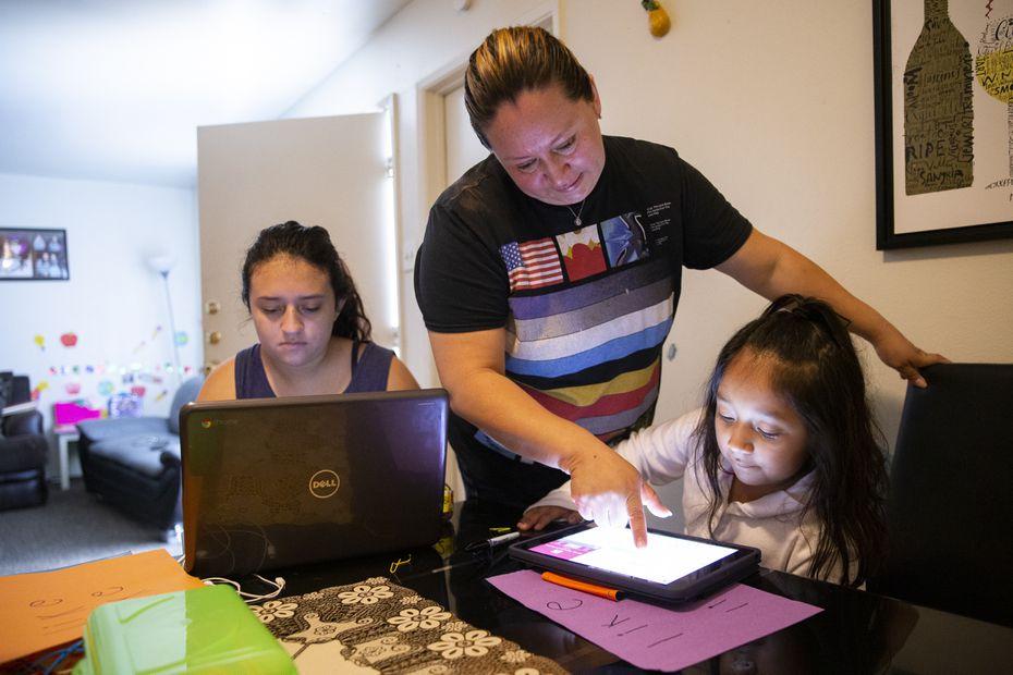 Hebreny Cojulum, de 19 años, asiste a su clase de física y química mientras su madre, Adali Arriaza, ayuda a su hermana Daysha, de 5 años, con su tarea. Las hermanas usas el internet de teléfonos celulares.