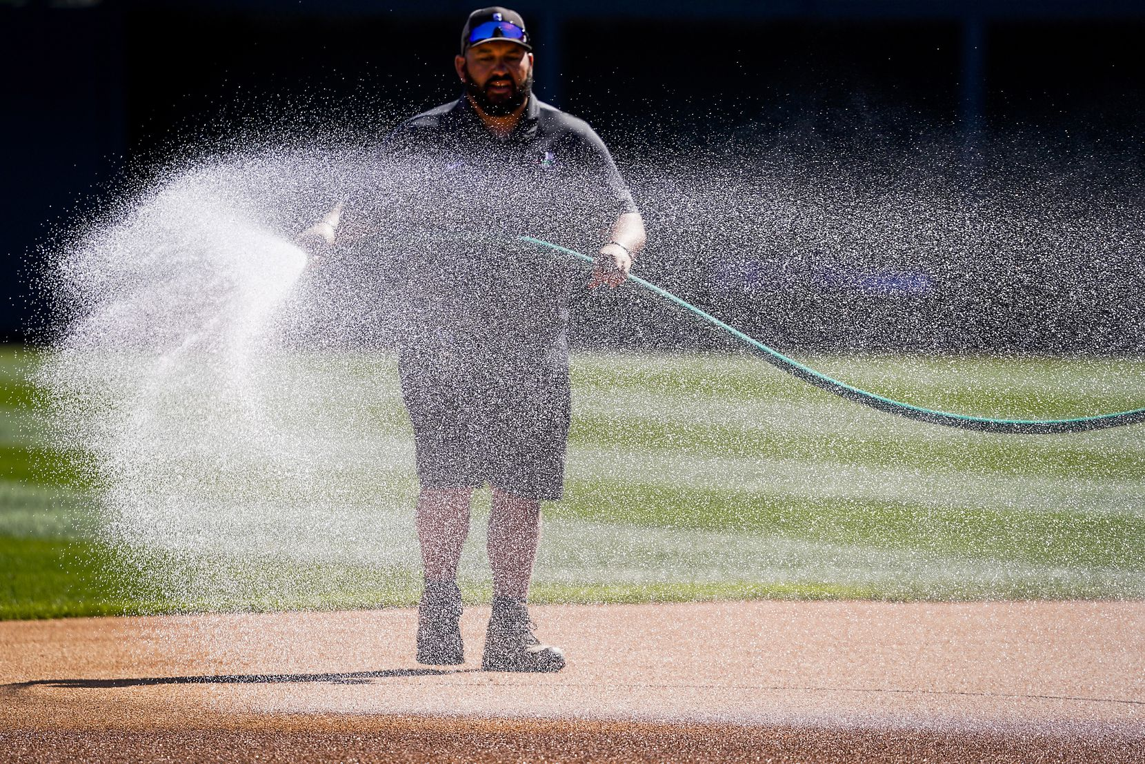 Groundkeepers prepare the field before a spring training game between the Texas Rangers and the Colorado Rockies at Salt River Fields at Talking Stick on Wednesday, Feb. 26, 2020, in Scottsdale, Ariz.