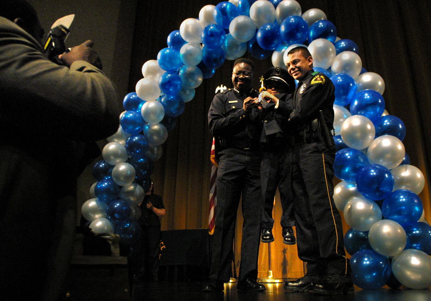 Former Dallas Police Chief Terrell Bolton, left, and newly-promoted senior corporal Joe R. Ramos, Jr., right, give Joe's son Christian Ramos, 6, a boost for a photo taken by senior corporal Chris Gilliam, far left, during the Dallas Police Department promotion ceremony at the Dallas Black Academy of Arts and Letters in downtown Dallas in 2002.