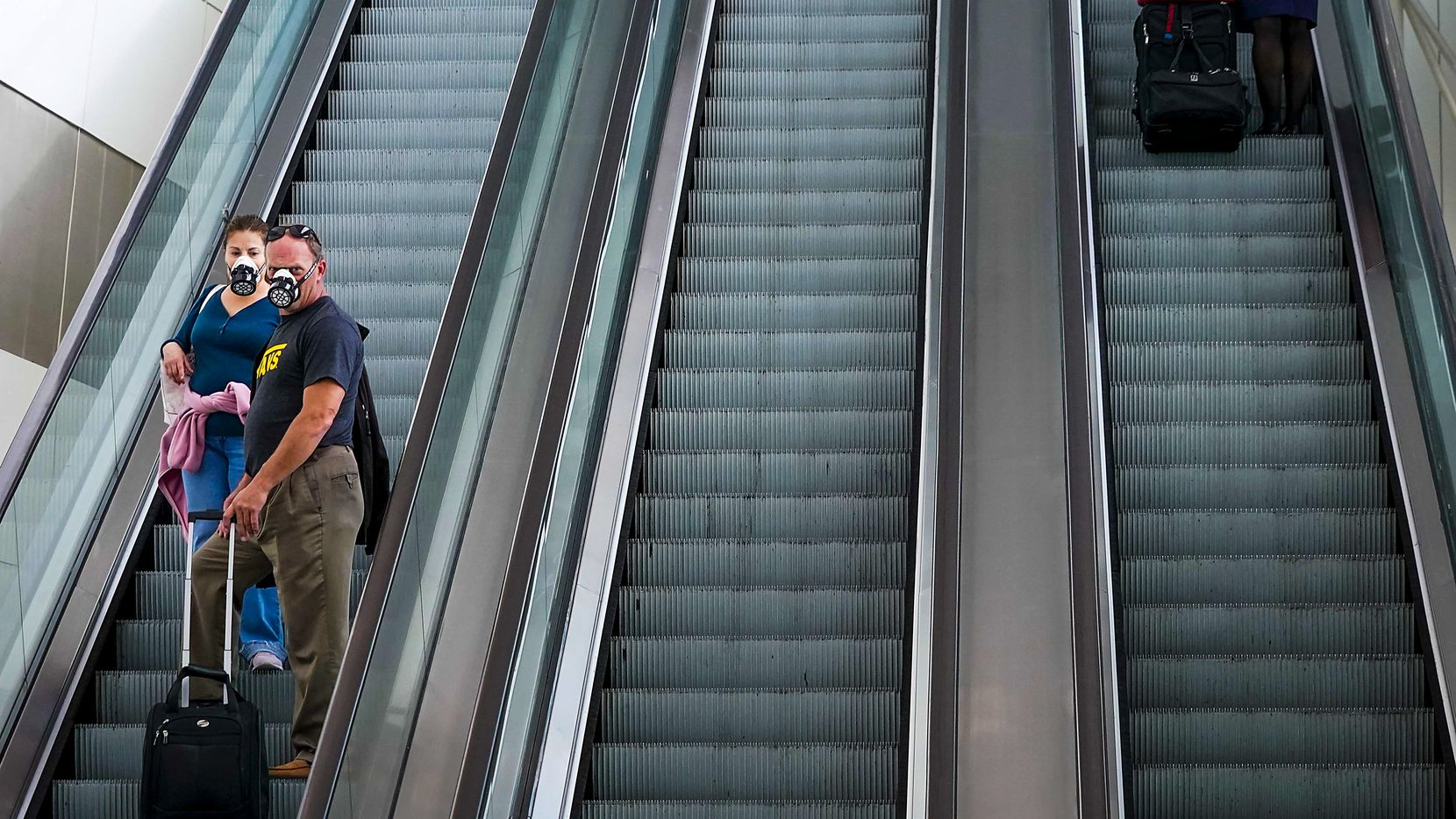 Passengers wearing face masks due to the new coronavirus ride an escalator at at  Dallas Fort Worth International (DFW) Airport Terminal B on Friday, March 20, 2020. For the day TSA reported 593,167 travelers nationwide, down from 2,559,307 on the same date in 2019.