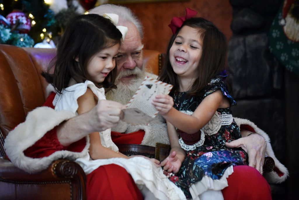 Santa Claus (Carl Anderson) shows a couple of Christmas letters to Reece Carrasco (left), and Reagan Carrasco, both 6, of Lucas on Nov. 26, 2018.